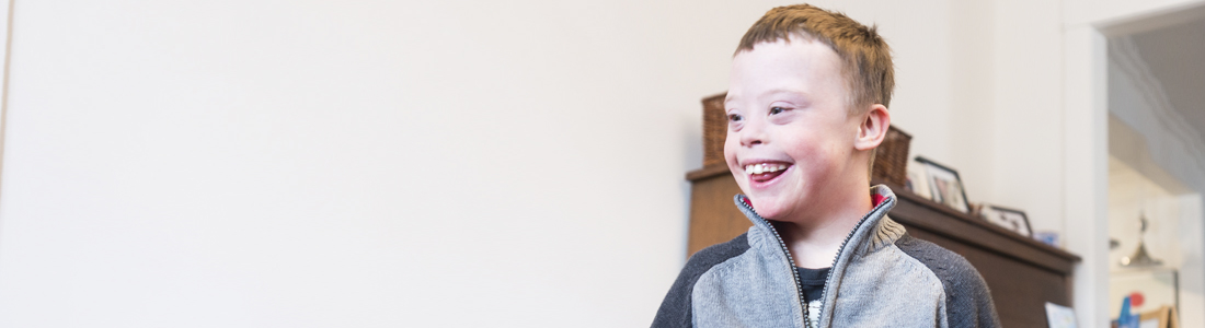 Young boy in a wheelchair with brown hair smiling