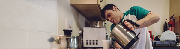 young man boiling the kettle in his kitchen