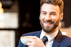 Man in navy suit smiling and holding a cup of coffee.