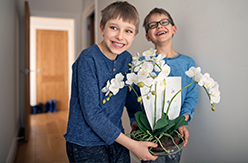Two young boys smiling at the camera holding a green plant and flower
