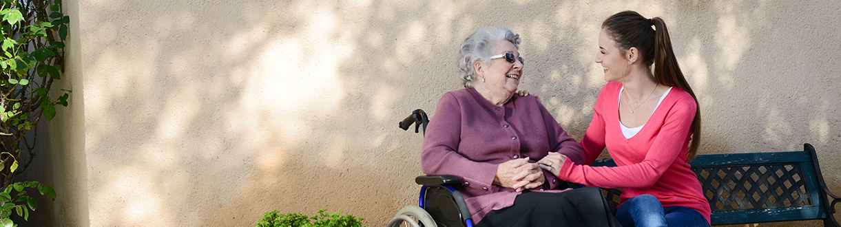 An elderly woman sitting outside with a palliative care worker.