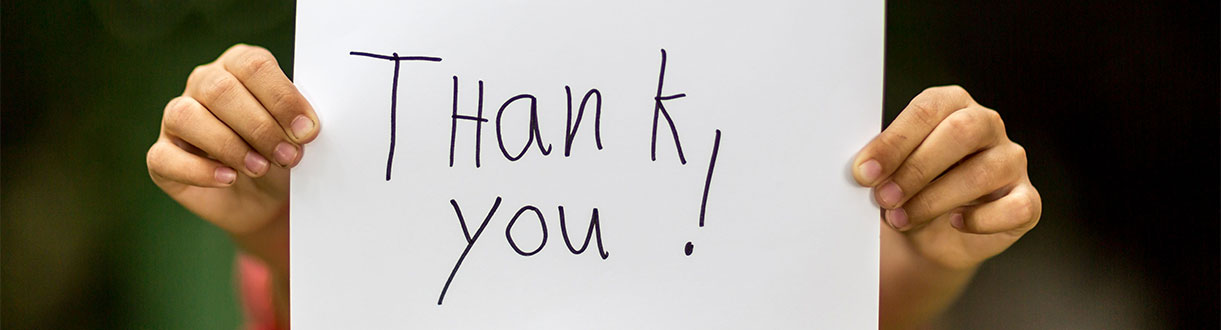 A thank you sign being held up by an unseen person.