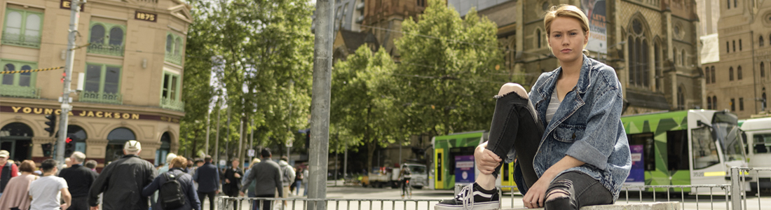 Photo of a young woman sitting outside in Melbourne's CBD