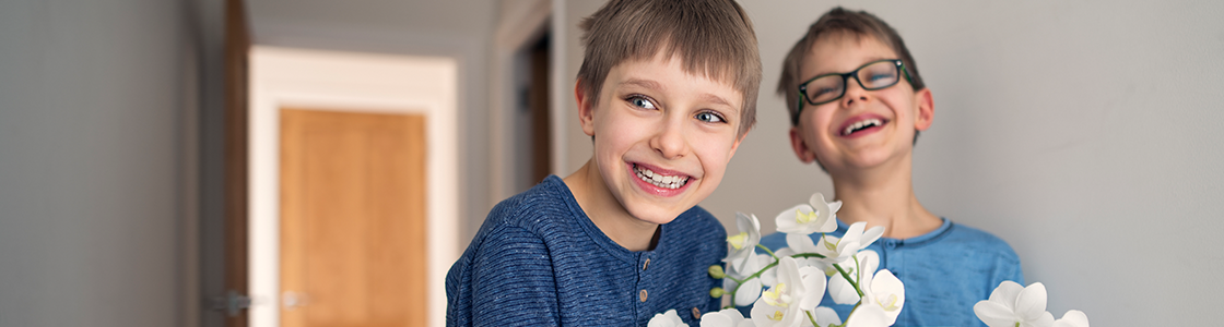 Two young boys holding some flowers and smiling